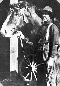 a man stands next to his horse holding its harness, pipe in his teeth